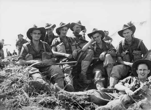 A group portrait of members of A Company, 2/8 Infantry Battalion, resting around a shell crater in the Wewak area (AWM 094025).
