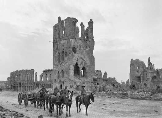 A loaded limber passing the ruins of the Cloth Hall at Ypres (AWM E00717).