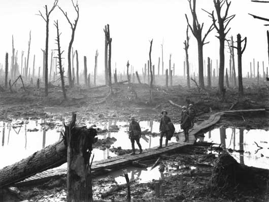 Australian members of a field artillery brigade passing along a duckboard track in the devastated Chateau Wood (AWM E01220).