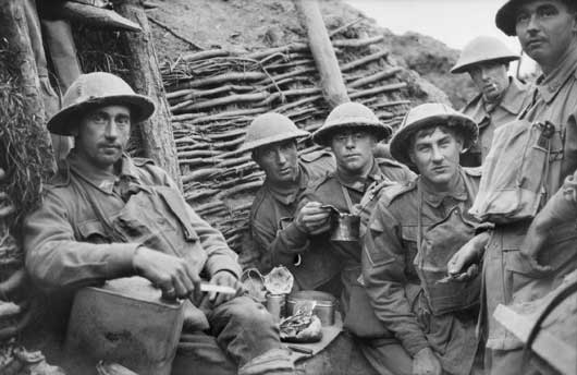 Members of the 22nd Battalion, AIF, taking a meal in the trenches on the night before the opening Australian attack in the Third Battle of Ypres (AWM E00739).