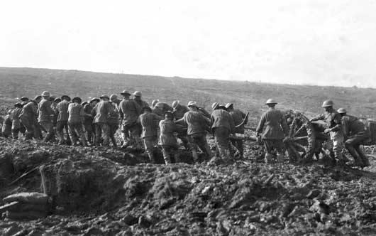 A gun of the 1st Australian Field Artillery Brigade being pushed over the boggy ground at Anzac Ridge (AWM E01056).