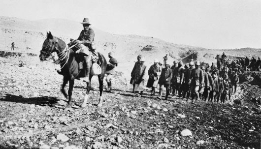 A large group of Turkish prisoners, being led by an Australian soldier of the Light Horse on horseback (AWM P02572.005).
