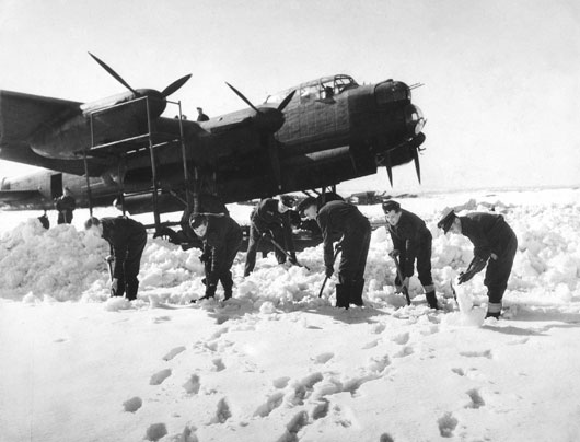 Allied air force members shovelling snow off a runway in front of a Lancaster bomber aircraft at Fiskerton RAF Station, Lincolnshire (AWM P00811.010).