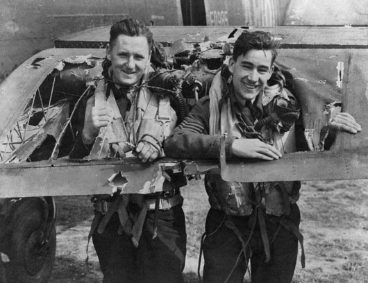 Two crewmembers of 460 Squadron RAAF demonstrate the size of a hole in the tail plane of their aircraft, badly damaged by an enemy night fighter during a highly successful raid (AWM UK0393).