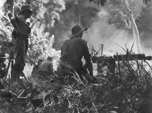 Members of the 2/2 Machine Gun Battalion firing on a native village housing 200 Japanese soldiers (AWM 109534).