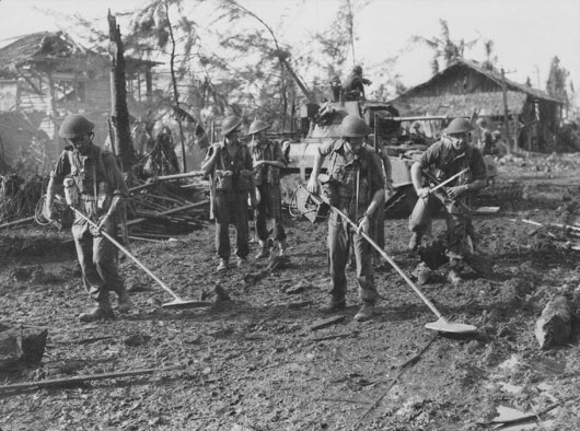 Australian soldiers searching for mines shortly after landing at Balikpapan (AWM 110379).