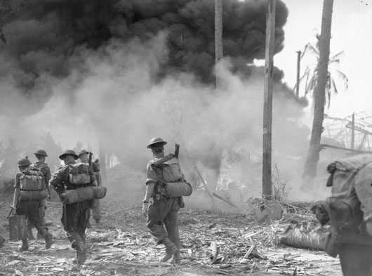 Troops move along Vasey Highway during the Oboe 2 operation, as oil fires blaze in the background (AWM 110383).