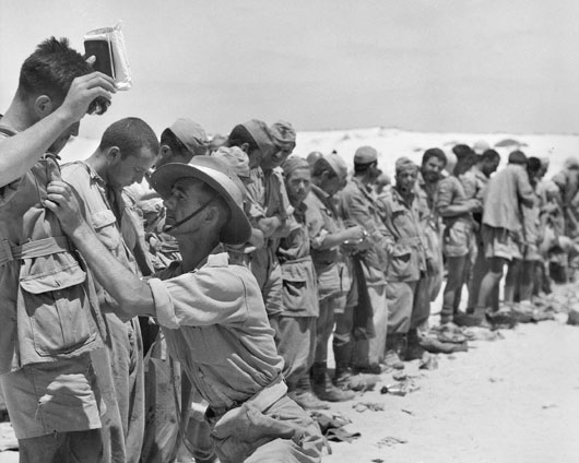 Italian prisoners of war being searched by a provost of the 9th Australian Divisional Provost Company (AWM 024537).