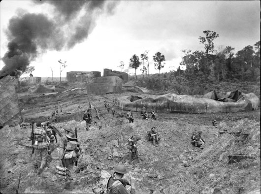 A Company, 2/23 Infantry Battalion, advancing through wrecked oil storage tanks at Tank Hill, Tarakan (AWM 090932).