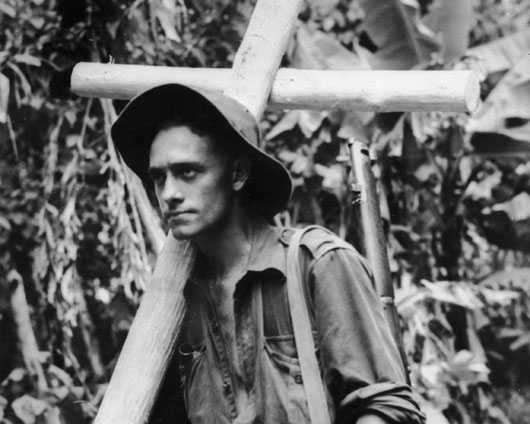 An Australian infantryman carries a cross hewn from rough forest timber to a forward position to mark the burial place of a fallen comrade (AWM 018176).