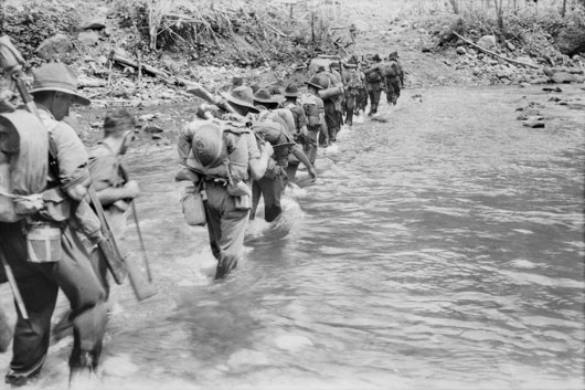 Troops of the 9th Infantry Battalion cross the Laruma River as they move forward to take over positions occupied by American soldiers (AWM 077250).