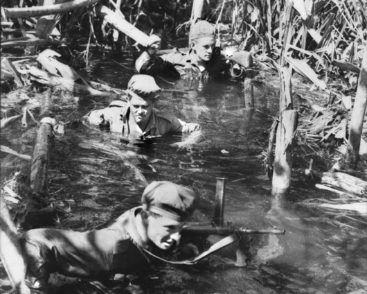 Members of a contact patrol negotiate a section of swamp during a patrol towards enemy territory (AWM 078546).