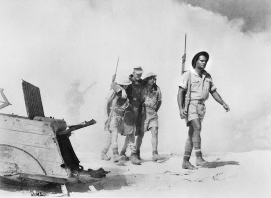 Two Australian soldiers help a wounded German following an attack on a German strongpoint at El Alamein (AWM 042075).