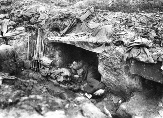 An Australian soldier sleeping in his trench shelter during fighting near Bullecourt (AWM E00455).