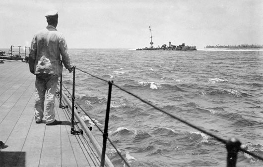 An unidentified seaman on the deck of HMAS Sydney looks at the wrecked German cruiser Emden, run ashore on North Keeling Island (AWM EN0401).