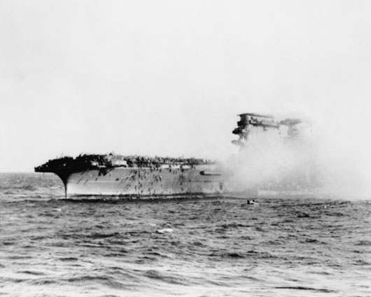 US Navy aircraft carrier Lexington on fire as crewmembers abandon ship (AWM 157901).