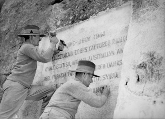 An enscription being cut into a cliff to record the capture of Damascus by Allied troops (AWM 012749A).