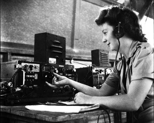 Signalwoman N. Overend tuning a No. 4 set at a receiving and transmitting centre at Katherine, Northern Territory (AWM 088627).