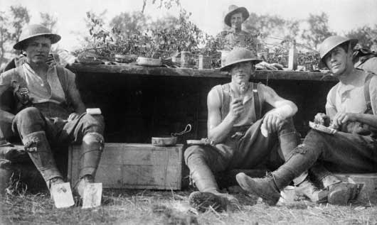 A group portrait of four artillery drivers, at their shelter during the Somme offensive (AWM C00474).