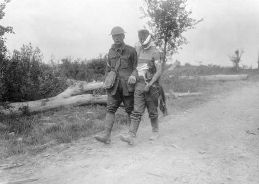 An Australian stretcher bearer assisting a wounded German prisoner during the Battle of Messines (AWM E00481).