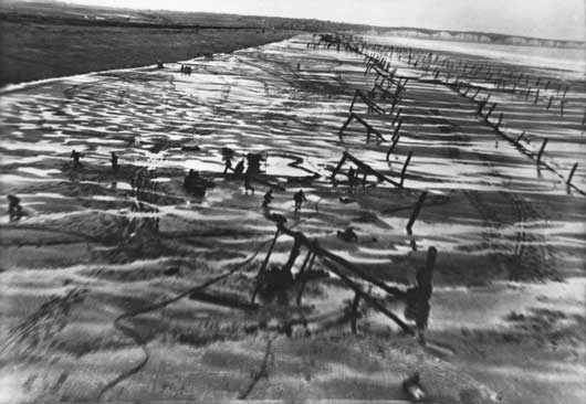 German troops working on beach defences scatter for cover after being startled by a low level RAF reconnaissance flight (AWM 128302).