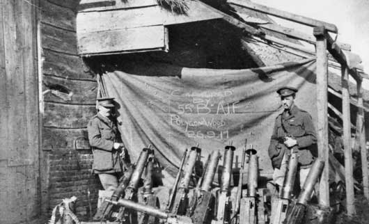 Two Australian officers with some of the German machine guns captured by the 55th Battalion in the attack near Ypres by the 5th Division on 26 September 1917 (AWM C01085).