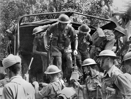 Australian troops alighting from a truck during the Allied retreat to Singapore (AWM 011303/29).