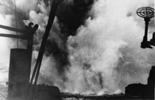 Water sprays into the air from a near miss during an attack on HMAS Perth by German bomber aircraft during the evacuation of Australian soldiers from Greece (AWM 306799).